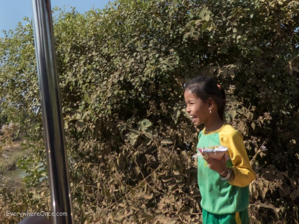 A Cambodian girl laughs hysterically with her friends after waving to us as we passed by in our tuk-tuk